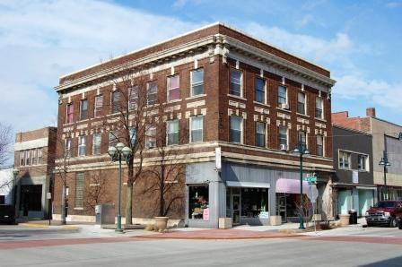 three story corner commercial building in brick with classical details