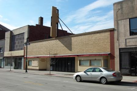 one story 1950s storefront with brick veneer facade
